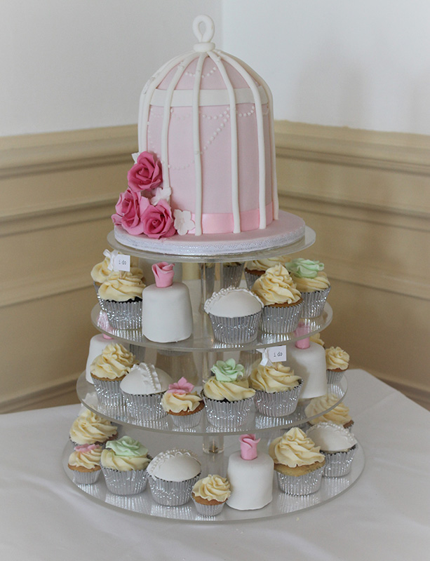 Birdcage top cake with a tower of cupcakes below