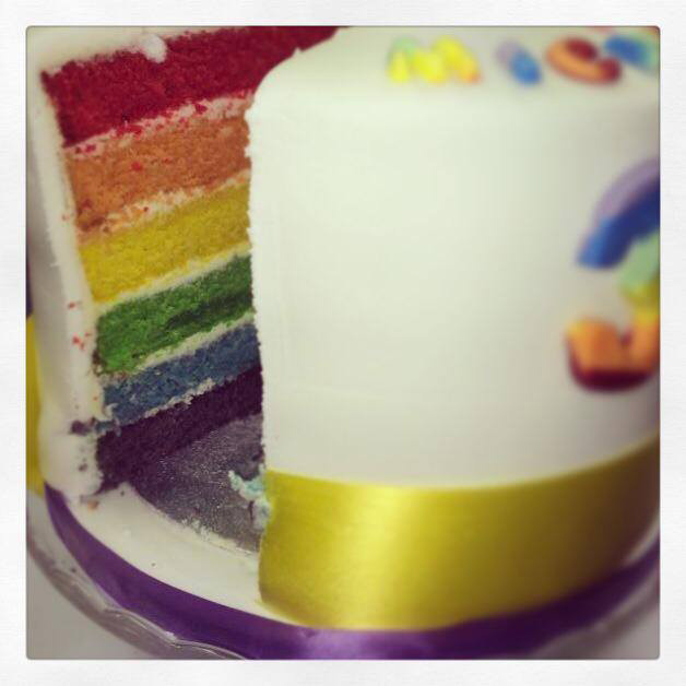 Rainbow cake with a slice take out