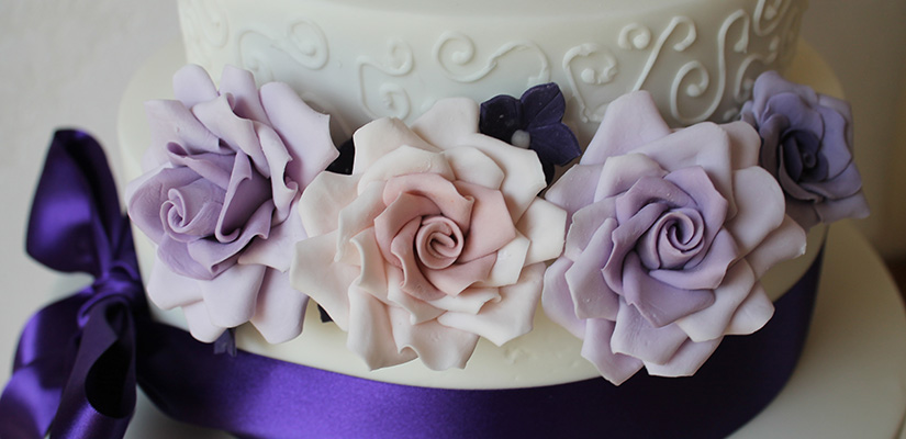 Three tier wedding cake with a purple bow and lilac roses