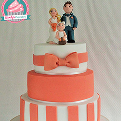 3 tier orange and white wedding cake with models of the family