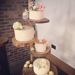 4 tier wedding cake split over a wooden stand